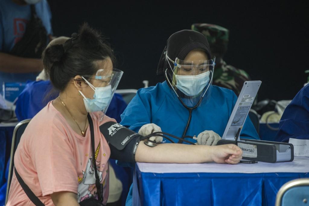 Nhân viên y tế kiểm tra một người phụ nữ trước khi tiêm vaccine Sinovac ngày 24/6. Ảnh: AFP.